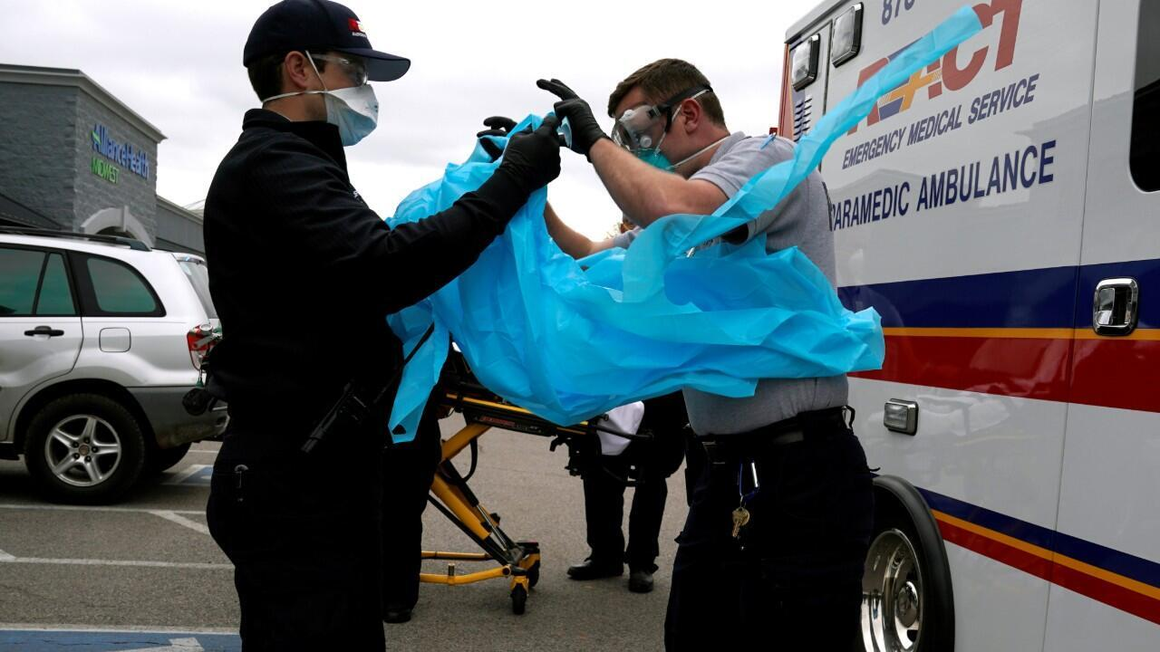 REACT EMS paramedics put on protective gear before making contact with a potential coronavirus disease (COVID-19) patient in Shawnee, Oklahoma, U.S. April 2, 2020.