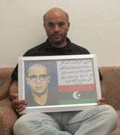 Salem Ziu holds a framed picture of his brother, Mehdi Ziu, who rammed his explosives-packed car through one of the main gates of the Katiba on Feb. 20.