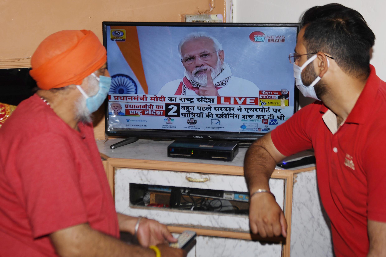 Unos habitantes de Amritsar ven el 14 de abril de 2020 por televisión al primer ministro, Narendra Modi, dirigiéndose a la nación India.