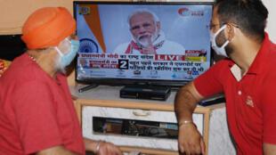 Des habitants de Amritsar regardent à la télévision le Premier ministre indien Modi, le 14 avril 2020.