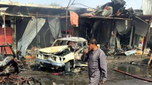 Un bombero camina por la zona en la que explotó el coche bomba tras el atentado en la ciudad de Qayyarah, Irak, el 23 de octubre de 2018.