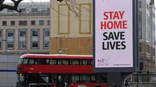 """نظرة عامة أثناء مرور حافلة أمام لوحة إعلانية تعرض رسالة """"البقاء في المنزل ينقذ الأرواح"""" في لندن، بريطانيا، 28 مارس/ آذار 2020."""