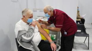 Un infirmier à la retraite injecte une dose de vaccin AstraZeneca à un patient à Blackpool (nord-ouest de l'Angleterre) le 25 janvier 2021