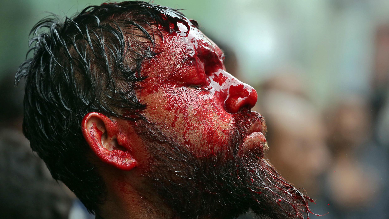 Un musulmán chiíta con la cabeza y la cara cubiertas de sangre se detiene después de flagelarse durante una procesión de Muharram para conmemorar a Ashura en Chennai, India, el 21 de septiembre de 2018.