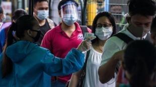 موظفة تقيس درجات حرارة راكبة قبل صعودها على متن حافلة في محطة قطارات في مانيلا في 7 تموز/يوليو 2020.