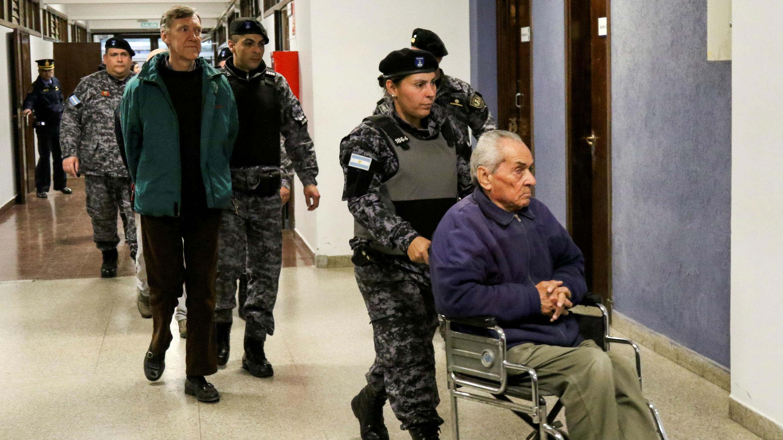 Los sacerdotes Nicola Corradi (R) y Horacio Corbacho son escoltados fuera de la sala del tribunal en Mendoza, Argentina , el 5 de agosto de 2019.