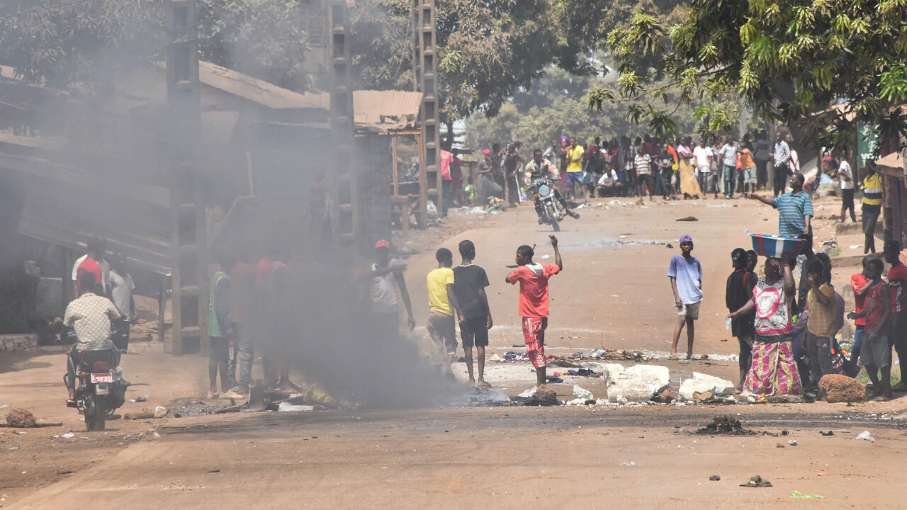 """Protesters burn rubbish and block roads along the """"axis of democracy"""" after protests broke out in Conakry on February 29, 2020. Guinea's President Alpha Conde announced on February 28, 2020 a """"slight postponement"""" of March 1's referendum on whether to adopt a new constitution, following mounting international criticism over the poll's fairness."""
