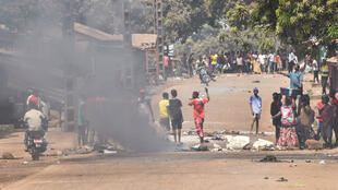 """Protesters burn rubbish and block roads along the """"axis of democracy"""" after protests broke out in Conakry on February 29, 2020. Guinea's President Alpha Conde announced a """"slight postponement"""" of a referendum on whether to adopt a new constitution."""
