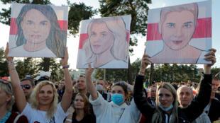 Personas sostienen retratos de Svetlana Tikhanouskaya, candidata en las próximas elecciones presidenciales, Veronika Tsepkalo, esposa del político Valery Tsepkalo, y Maria Kolesnikova, representante de la oficina de campaña del político Viktor Babariko, durante un mitin de campaña electoral en Borisov, Belorús el 23 de julio de 2020.