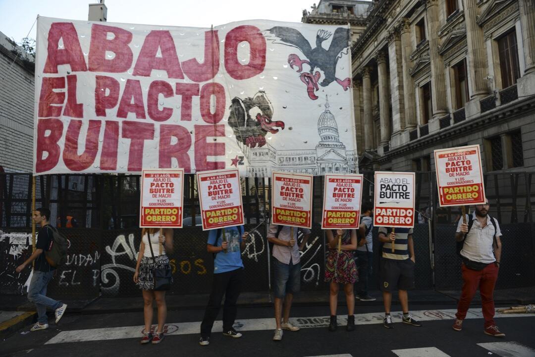 """Un grupo de manifestantes sostienen carteles que dicen """"Abajo el acuerdo del buitre"""", mientras que los senadores argentinos debaten un acuerdo para pagar a los acreedores descontentos, mientras el gobierno busca poner fin a una batalla de 15 años en los tribunales estadounidenses por un incumplimiento catastrófico de la deuda, fuera del Congreso Nacional en Buenos Aires el 30 de marzo de 2016."""