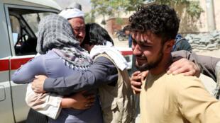 Hombres afganos se consuelan, el 18 de agosto de 2019, mientras lloran durante el funeral de sus familiares después de la explosión de una bomba suicida en una boda en Kabul, ocurrida un día antes.