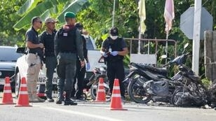 Police inspect the scene of a deadly attack by suspected rebels at a military outpost in Pattani, southern Thailand.