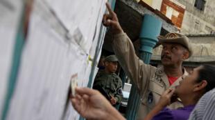 Personas revisan una lista electoral en una estación de voto durante las elecciones municipales venezolanas, Caracas, 10 de diciembre de 2017