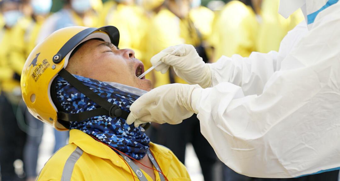 Un equipo médico realiza un test de coronavirus a un trabajador de servicios postales en Beijing, China, el 19 de junio de 2020.