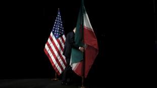 موظف يزيل العلم الايراني من على المسرح بعد صورة جماعية مع وزراء خارجية وممثلين عن الولايات المتحدة وإيران والصين وروسيا وبريطانيا وألمانيا وفرنسا والاتحاد الأوروبي خلال المحادثات النووية الايرانية في مركز فيينا الدولي بفيينا ، النمسا ، 14 يوليو 2015.