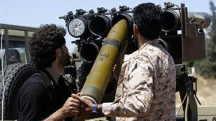 Des combattants fidèles au GNA chargent un canon, à Espiaa, à environ 40 kilomètres au sud de Tripoli, le 29 avril 2019.