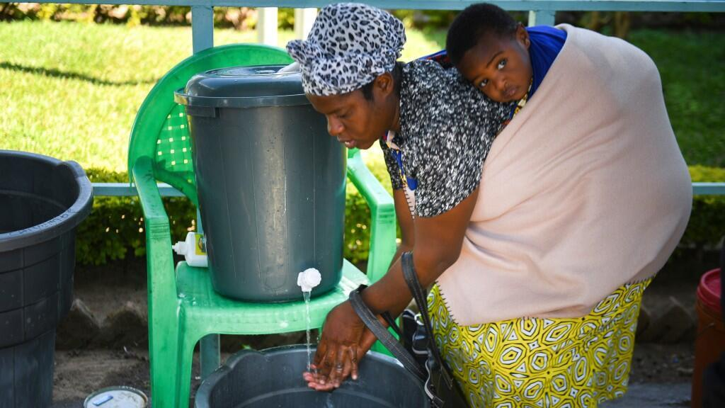 Una madre está cargando a sus espaldas a un niño pequeño en plena pandemia del coronavirus. Imagen de Blantyre, en Malawi, el 23 de junio de 2020.