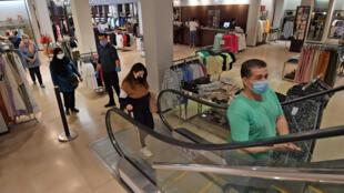 Unos clientes guardan la distancia social en una tienda de ropa de Túnez el 12 de mayo de 2020