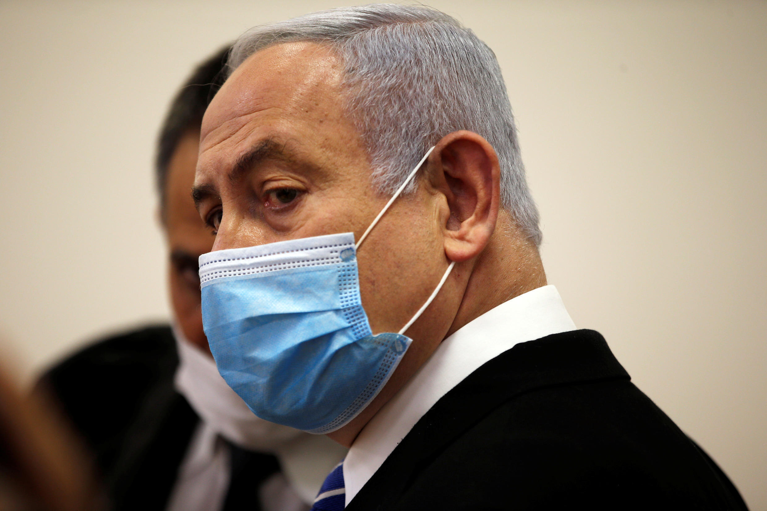 Israeli Prime Minister Benjamin Netanyahu, wearing a face mask, looks on while standing inside the court room as his corruption trial opens at the Jerusalem District Court May 24, 2020.