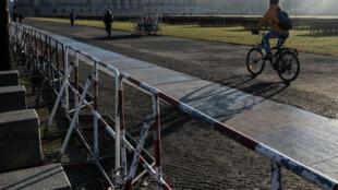 Un ciclista pasa al lado de unas vallas cerca al Bundestag, en medio del refuerzo de seguridad en Berlín por la cumbre internacional de Libia. 17 de enero de 2020.