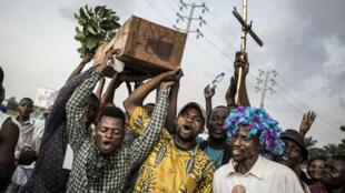 """Des supporteurs de Martin Fayulu portent un cercueil sur lequel il est inscrit """"Adieu Félix"""", dans une manifestation le 21 janvier 2019, à Kinshasa, la capitale de la RD Congo."""