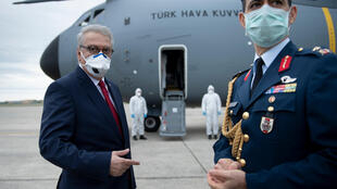 Turkey's ambassador to the United States, Serdar Kilic, waits as a Turkish cargo plane carrying COVID-19 relief supplies is unloaded at Andrews Air Force Base near Washington in April 2020