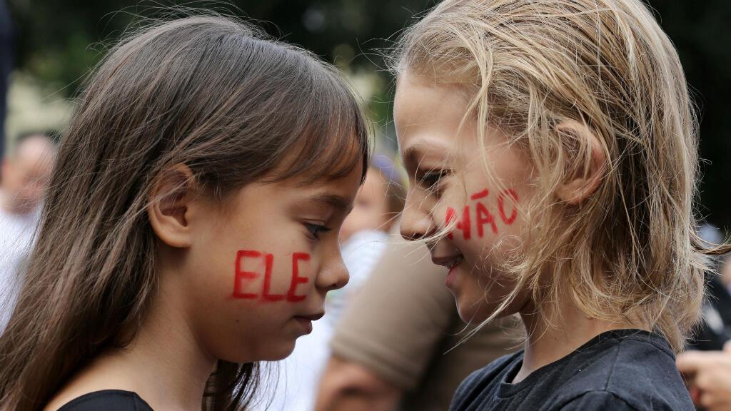 """Deux enfants lors d'une manifestation anti-Bolsonaro le 29 octobre 2018, le slogan """"Pas lui"""" peint sur le visage."""