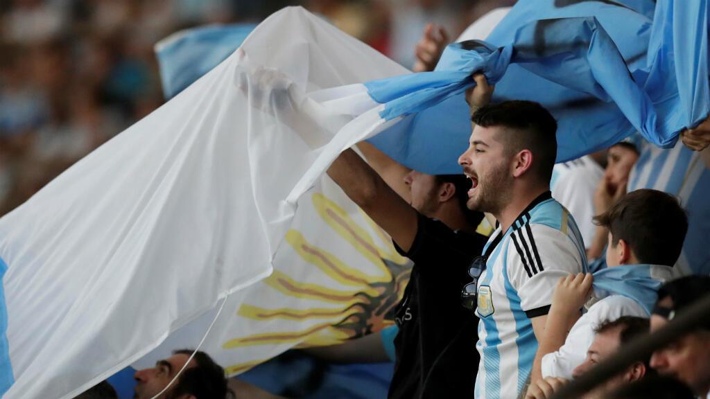 Hinchas argentinos celebran los goles de su selección en el Arena Do Gremio de Porto Alegre en Brasil, el 23 de junio de 2019.