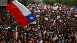 Des protestataires chiliens brandissent le drapeau national lors des manifestations à Santiago, le 25octobre2019.