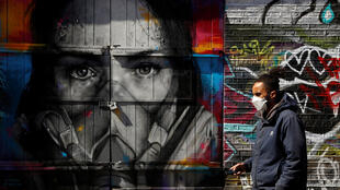 A man wearing a mask walks in Brick Lane in front of graffiti as the spread of the coronavirus disease (COVID-19) continues, London, Britain, April 14, 2020.