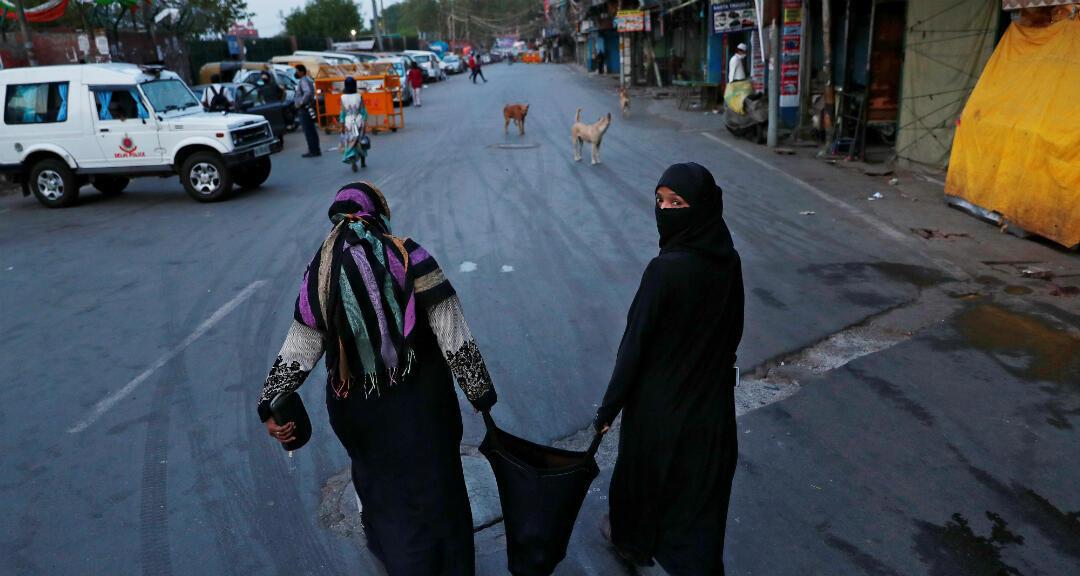Mujeres musulmanas llevan una bolsa después de comprar alimentos en la víspera del mes de ayuno sagrado del Ramadán, durante un bloqueo nacional para frenar la propagación de la enfermedad por coronavirus (Covid-19), en Delhi, India, el 24 de abril 2020.