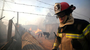 Un bombero camina cerca de una vivienda en llamas en los incendios en Valparaíso, el 24 de diciembre de 2019.