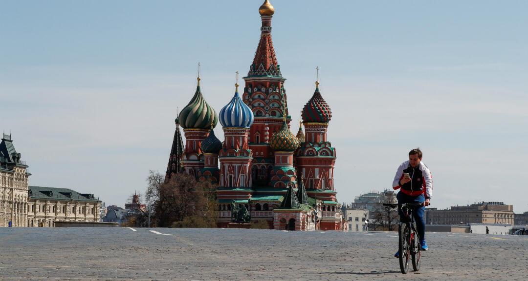 Un hombre monta en bicicleta en la Plaza Roja de Moscú, vacía en un 1 de mayo inaudito y marcado por el coronavirus. Moscú, Rusia, el 1 de mayo de 2020.