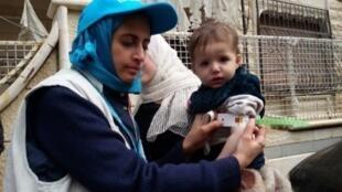 """موظفة من """"يونيسف"""" تعاين طفلا يعاني من سوء التغذية في مضايا، 14 كانون الثاني/يناير 2016"""