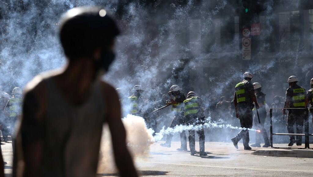 Un hombre pasa cerca de agentes de la policía, en medio de gases lacrimógenos, durante una protesta contra el presidente brasileño Jair Bolsonaro, en la avenida Paulista, en Sao Paulo, Brasil, el 31 de mayo de 2020.
