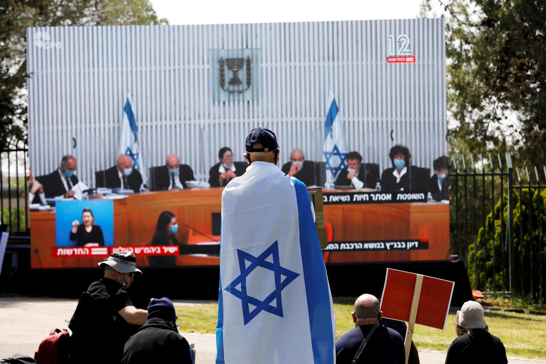 إسرائيليون يحتجون أمام لافتة عليها صورة قضاة المحكمة العليا خارج الكنيست، في القدس 3 مايو/ أيار 2020