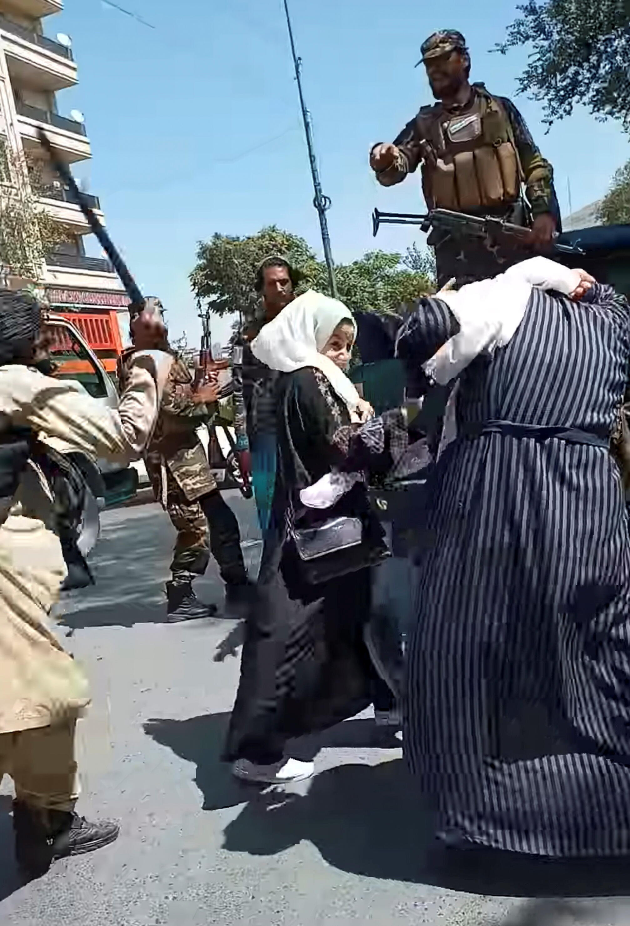 A Taliban soldier beats women protesting in Kabul, September 8, 2021 in this picture obtained from social media video.