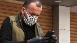 Un refugiado palestino con mascarilla y guantes protectores mira su teléfono móvil el 26 de marzo de 2020 en la ciudad de Sidón, al sur del Líbano