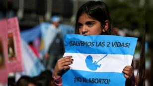"""Una niña sostiene una pancarta con la consigna """"Salvemos las 2 vidas"""", durante una manifestación en contra del aborto. En Buenos Aires, Argentina, el 4 de agosto de 2018."""