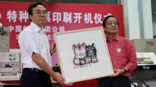 Le designer Han Meilin remets son illustration à Liu Aili, président de la poste chinoise.