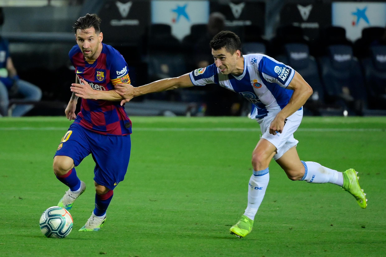 نجم برشلونة الأرجنتيني ليونيل ميسي (يسار) متخطيا منافسه من إسبانيول ماركو روزا خلال لقاء الفريقين في الدوري الإسباني. 8 تموز/يوليو 2020