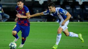 نجم برشلونة الارجنتيني ليونيل ميسي (يسار) متخطيا منافسه من اسبانيول ماركو روزا خلال لقاء الفريقين في الدوري الاسباني. 8 تموز/يوليو 2020