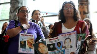 Las mujeres tienen carteles durante la ceremonia de clausura de la Investigación Nacional sobre Mujeres y Niñas Indígenas Desaparecidas y Asesinadas en Quebec, Canadá , 3 de junio de 2019.
