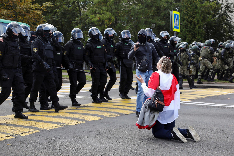 Un manifestant s'agenouillant devant des agents des forces de l'ordre lors d'un rassemblement contre les violences policières à Minsk, le 13 septembre 2020.