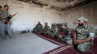 عضو في قوات الحشد الشعبي يشرح كيفية استخدام الأسلحة كجزء من التدريب العسكري بمعسكر في البصرة، العراق- 4 أغسطس/آب 2019
