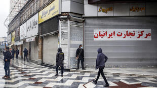 People walk past closed shops in Tehran on Saturday as authorities announced new measures to curb the spread of the novel coronavirus