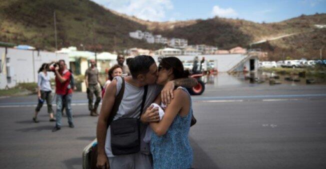 Un couple avec son bébé s'embrasse avant d'être évacué de l'île de Saint-Martin après le passage de l'ouragan Irma, le 10 septembre 2017 à l'aéroport de Grand-Case.