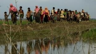 لاجئون من الروهينغا فروا من ولاية راخين في بورما يعبرون بلدة اوخيا الحدودية قرب بنغلادش، الاثنين 4 ايلول/سبتمبر 2017