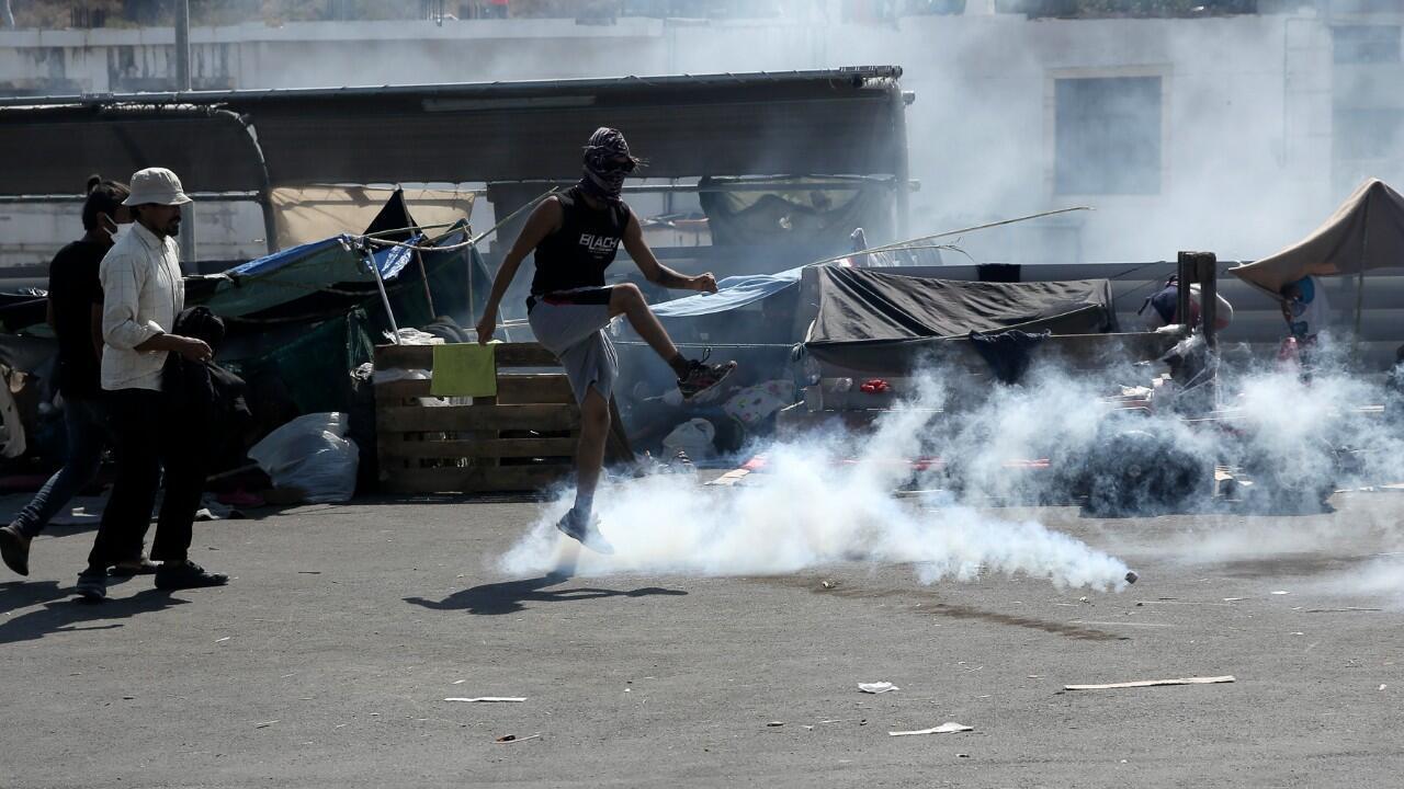 Un hombre patea un bote de gas lacrimógeno durante enfrentamientos menores entre la policía antidisturbios y los migrantes cerca de la ciudad de Mytilene, en la isla nororiental de Lesbos, Grecia, el sábado 12 de septiembre de 2020.