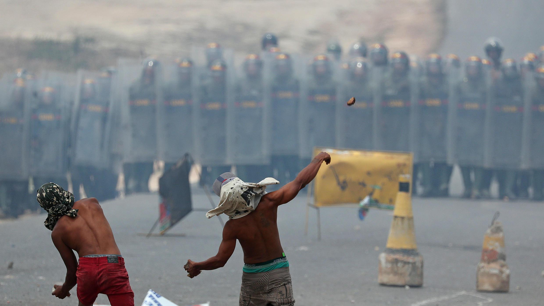 Manifestantes lanzan piedras a una línea de guardias nacionales venezolanos en la zona fronteriza de Pacaraima, Brasil, el 24 de febrero de 2019.